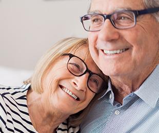 happy senior couple in matching eyeglasses